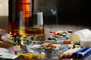 beer, needles, cigarettes, and pills indicate alcohol and drug abuse