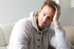 man in hoodie with headache goes through THC Detox